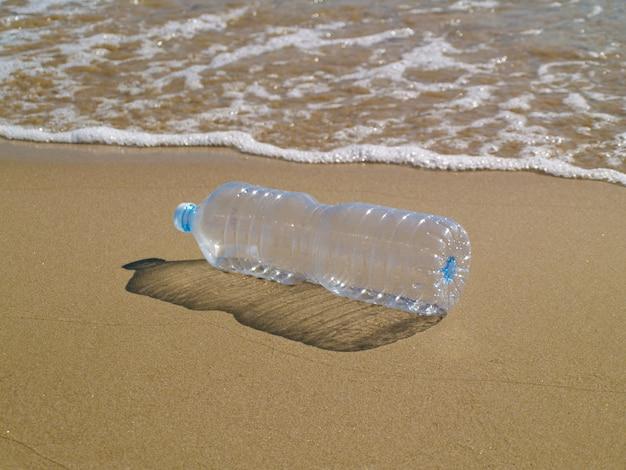 Plastikflasche auf dem sand am strand, plastik reduzieren, wiederverwenden und recyceln