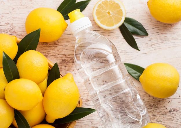 Plastikflasche des bio-frischen sommerwassers der frischen zitrone mit rohen zitronen auf hellem holz. draufsicht