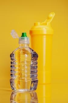 Plastikflasche mineralwasser auf einem hellen gelben hintergrund
