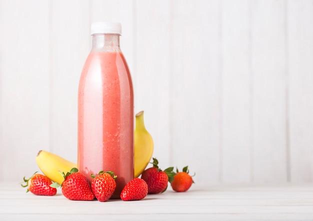 Plastikflasche mit frischem sommerbeeren-smoothie auf holztisch. erdbeer- und bananengeschmack.