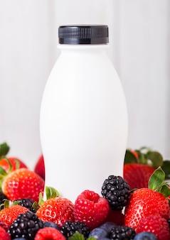 Plastikflasche mit frischem sommerbeeren-smoothie auf holztisch. erdbeeren und himbeeren mit blaubeeren und brombeeren.