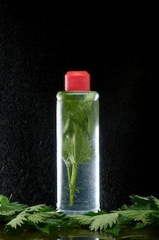 Plastikflasche mit frischer nessel in den wolken des wasserstaubs