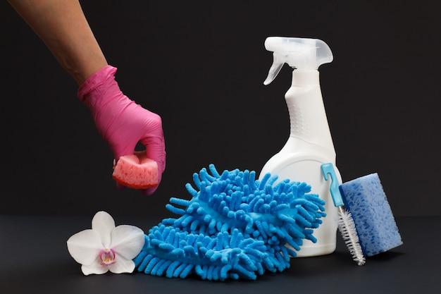 Plastikflasche mit spülmittel, ein lappen, eine orchideenblüte und eine hand mit einem schwamm auf schwarzem hintergrund. wasch- und reinigungsset.