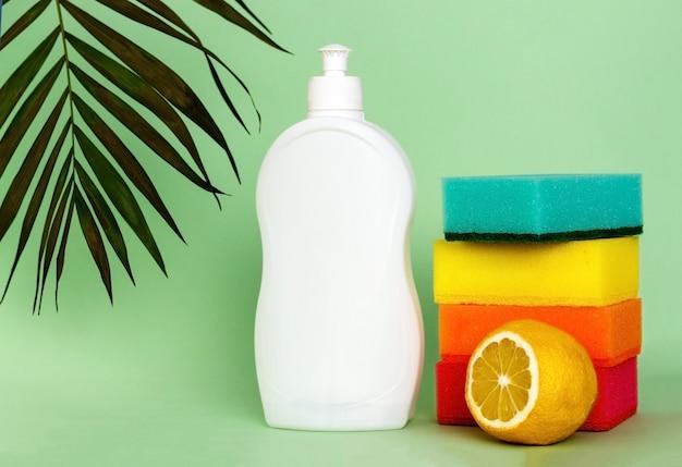 Plastikflasche spülmittel zitrone und schwämme auf farbhintergrund wasch- und reinigungskonzept