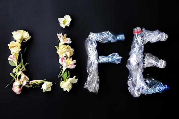 Plastikflasche und blumen machen ein wort. lebensentscheidung. verschmutzte welt. umweltproblem. ökologisches desaster. recyclingproblem.