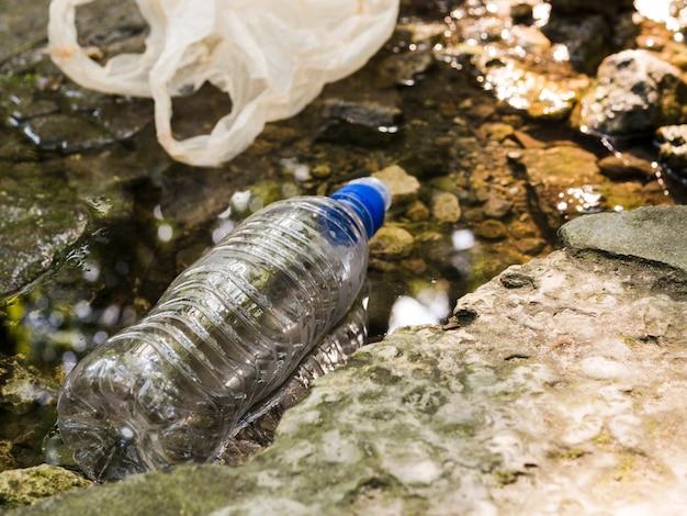Plastikflasche und tasche, die in wasser an draußen schwimmen