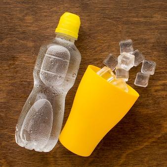 Plastikflasche wasser und eis in der tasse