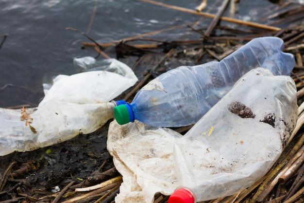 Plastikflaschen am flussufer, konzept für den tag des schutzes der ozeane. nicht abbaubarer plastikmüll an der küste.