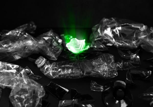 Plastikflaschen, die mit einer blume im stapel liegen. grünes leuchtendes licht. umweltverschmutzung. ökologisches desaster. recyclingproblem.