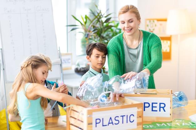 Plastikflaschen. lehrer und kinder stecken plastikflaschen in eine kiste, während sie im ökologieunterricht müll sortieren
