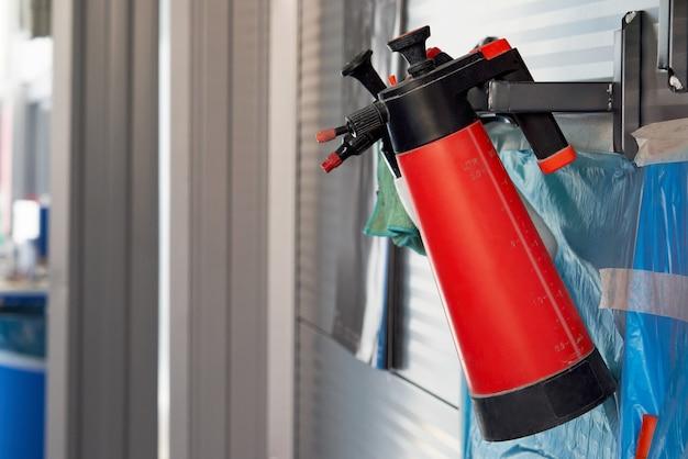 Plastikflaschen mit autospray hängen an der wand in der autowerkstatt
