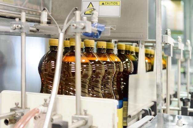 Plastikflaschen mit bier auf dem förderer einer automatischen verpackungsmaschine. die maschine verpackt bierflaschen in plastikfolie.