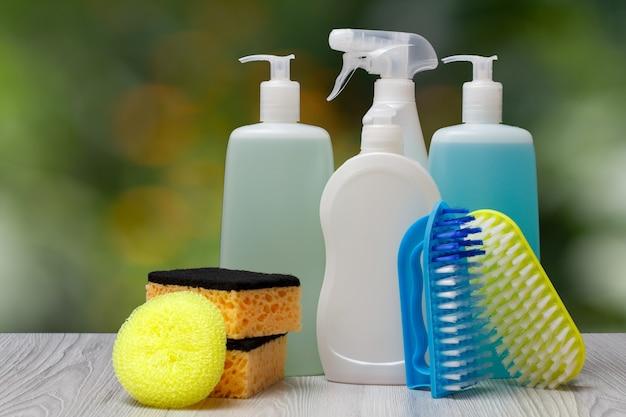 Plastikflaschen mit geschirrspülmittel, glas- und fliesenreiniger, reinigungsmittel für mikrowellenherde und herde, bürsten und schwämme auf dem verschwommenen natürlichen hintergrund. wasch- und reinigungskonzept.