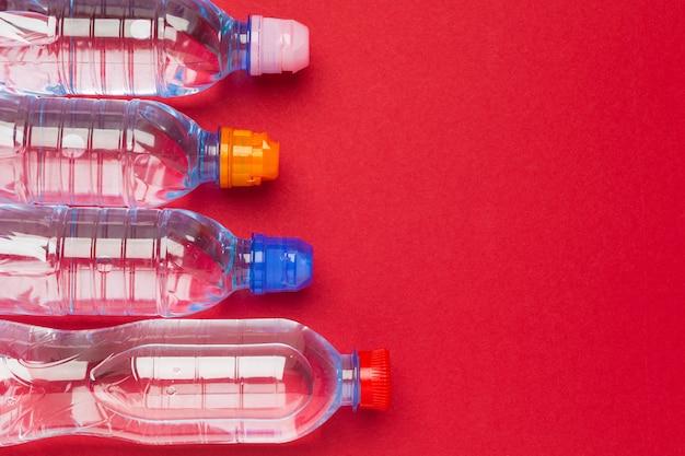 Plastikflaschen mit reinem wasser auf draufsicht des roten hintergrundes