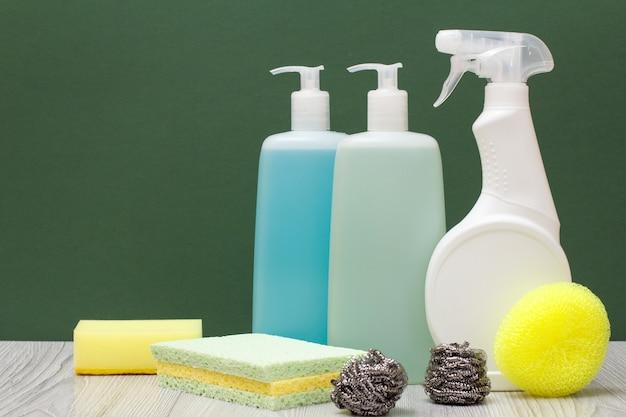 Plastikflaschen mit reinigungsmittel für mikrowellenherde und öfen, glas- und fliesenreiniger und schwämme auf grünem hintergrund. wasch- und reinigungskonzept.