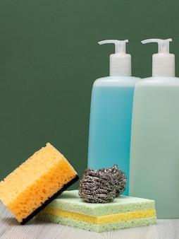 Plastikflaschen mit reinigungsmittel für mikrowellenherde und öfen, glas- und fliesenreiniger und schwämme im grünen hintergrund. wasch- und reinigungsmittel.