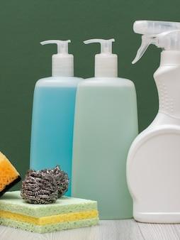 Plastikflaschen mit reinigungsmittel für mikrowellenherde und öfen, glas- und fliesenreiniger und schwämme mit grünem hintergrund. wasch- und reinigungsmittel.