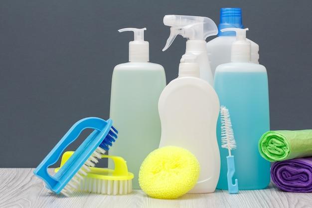 Plastikflaschen mit spülmittel, glas- und fliesenreiniger, reinigungsmittel für mikrowellenherde und öfen, bürsten, schwämme und müllsäcke auf grauem hintergrund. wasch- und reinigungskonzept.