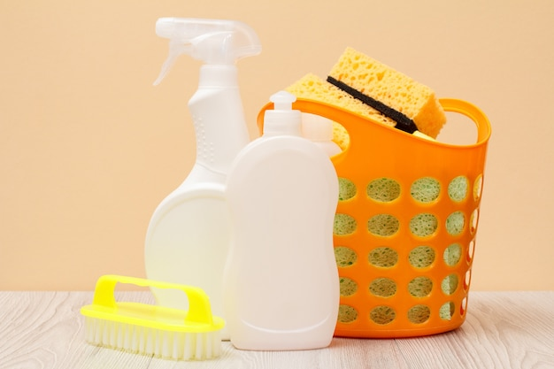 Plastikflaschen mit spülmittel, glas- und fliesenreiniger, reinigungsmittel für mikrowellenherde und öfen, korb, bürste, schwämme auf beigem hintergrund. wasch- und reinigungskonzept.