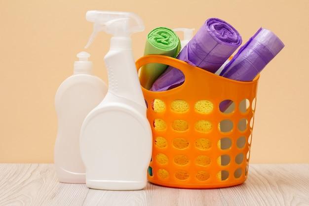 Plastikflaschen mit spülmittel, glas- und fliesenreiniger, reinigungsmittel für mikrowellenherde und öfen, korb, müllsäcke, schwämme auf beigem hintergrund. wasch- und reinigungskonzept.