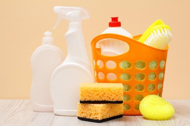 Plastikflaschen mit spülmittel, glas- und fliesenreiniger, reinigungsmittel für mikrowellenherde und öfen, korb, schwämme auf beigem hintergrund. wasch- und reinigungskonzept.