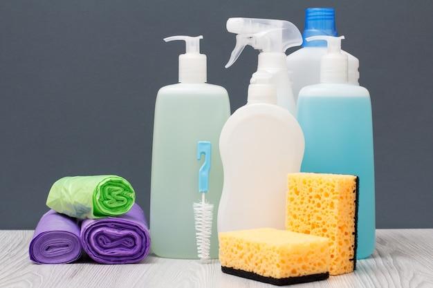 Plastikflaschen mit spülmittel, glas- und fliesenreiniger, reinigungsmittel für mikrowellenherde und öfen, müllsäcke und schwämme auf grauem hintergrund. wasch- und reinigungskonzept.