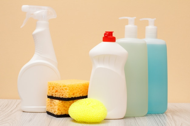 Plastikflaschen mit spülmittel, glas- und fliesenreiniger, reinigungsmittel für mikrowellenherde und öfen, schwämme auf beigem hintergrund. wasch- und reinigungskonzept.