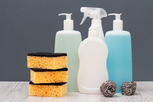 Plastikflaschen mit spülmittel, glas- und fliesenreiniger, reinigungsmittel für mikrowellenherde und öfen, schwämme auf grauem hintergrund. wasch- und reinigungskonzept.