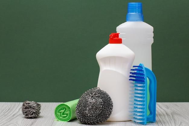 Plastikflaschen mit spülmittel, reinigungsmittel für mikrowellenherde und öfen, bürste, schwämme und müllsäcke auf grünem hintergrund. wasch- und reinigungskonzept.