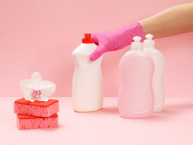 Plastikflaschen mit waschflüssigkeit, schwämme und eine hand in einem nitrilhandschuh mit einer flasche glas- und fliesenreiniger auf rosafarbenem hintergrund. wasch- und reinigungsset.
