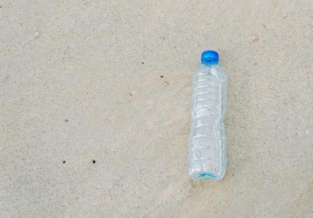 Plastikflaschenmüll auf dem menschlichen abfalltropfen des strandes