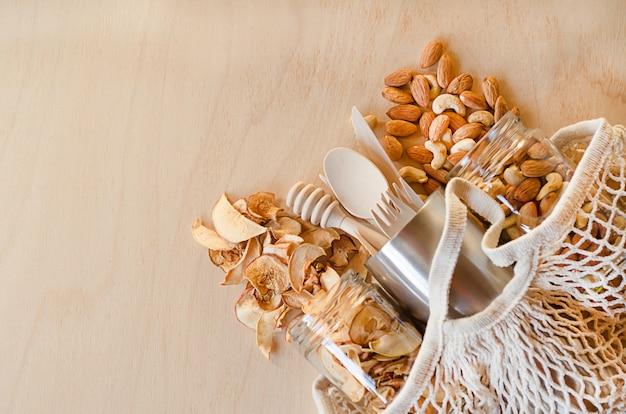 Plastikfreies küchenzubehör, getrocknete früchte und nüsse in gläsern, hölzernes küchenzubehör in metallflasche im stringbeutel.