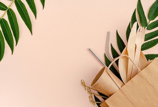 Plastikfreies set mit bambus, papierbesteck und metallstrohhalmen auf pink