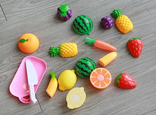 Plastikfrüchte auf hölzernem hintergrund, spielzeug der kinder