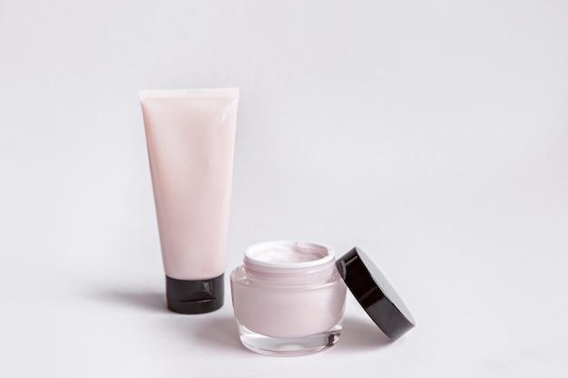 Plastikgefäß mit der gesichts- oder körpercreme lokalisiert auf weißem hintergrund