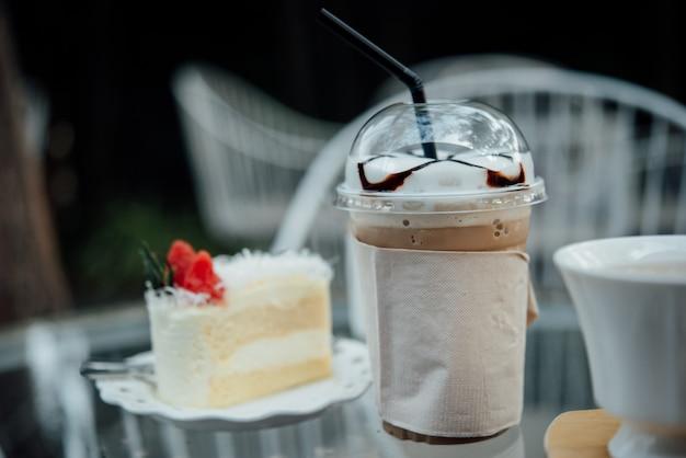 Plastikglas eiskaffee mit kuchen auf tabelle in der kaffeestube
