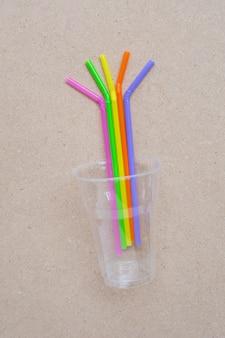 Plastikglas mit strohhalmen auf sperrholz