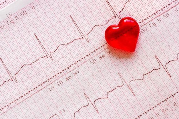 Plastikherz auf dem hintergrund des elektrokardiogramms (ekg). gesunder herztag