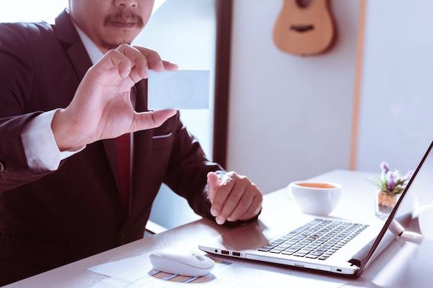 Plastikkarte in den händen, laptop, arbeitsplatz