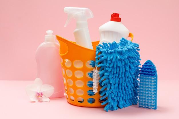 Plastikkorb mit flaschen spülmittel, glas- und fliesenreiniger, reinigungsmittel für mikrowellenherde und öfen, lappen, bürsten und schwämme auf rosafarbenem hintergrund. wasch- und reinigungsset.
