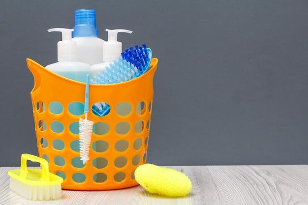 Plastikkorb mit flaschen spülmittel, glas- und fliesenreiniger, reinigungsmittel für mikrowellenherde und öfen mit bürste und schwämmen auf grauem hintergrund. wasch- und reinigungsset.