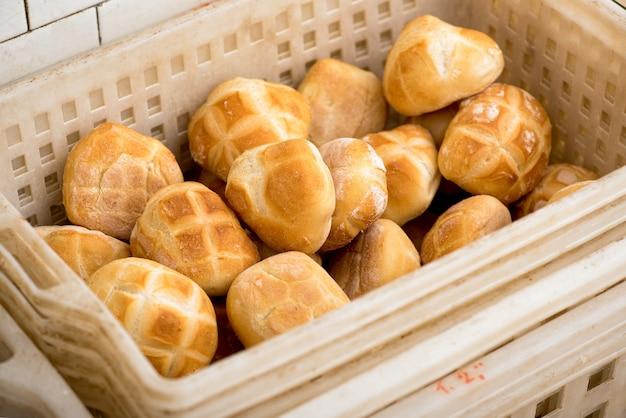 Plastikkorb mit frisch gebackenen brötchen