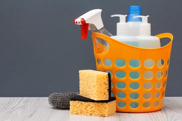 Plastikkorb mit schutzhandschuh, flaschen mit spülmittel, glas- und fliesenreiniger, reinigungsmittel für mikrowellenherde und öfen, schwämme auf grauem hintergrund. wasch- und reinigungskonzept.