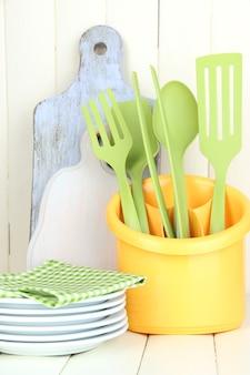 Plastikküchenutensilien in der tasse auf holztisch