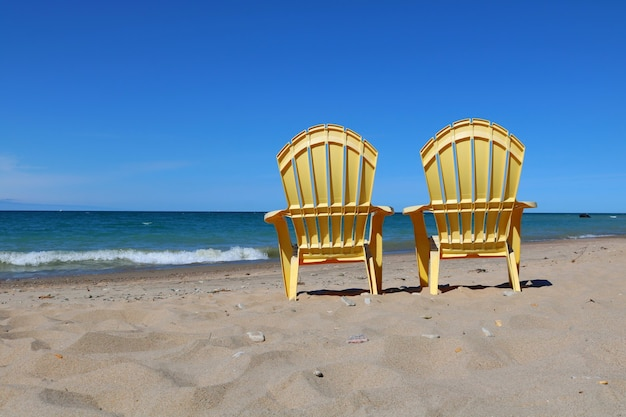 Plastikliegestühle am sandstrand