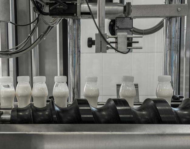 Plastikmilchflaschen auf förderband. ausrüstung in der molkerei