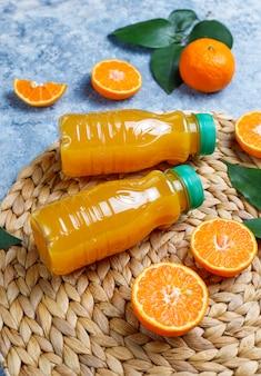 Plastikminiflaschen organischer frischer orangensaft mit rohen orangen und mandarinen