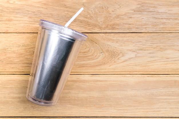 Plastikpokalschale der draufsicht mit stroh oder rohr auf hölzernem hintergrund