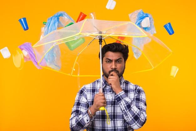 Plastikrecyclingproblem, umweltverschmutzung und umweltkatastrophenkonzept - ernster indischer mann, der über ökologie unter einem regenschirm auf gelbem hintergrund nachdenkt