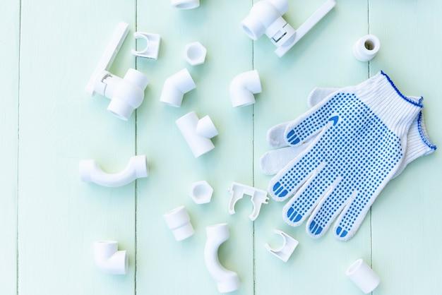 Plastikrohre, handschuhe auf einem hellblauen holztisch.